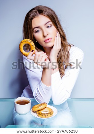 woman eating a bun, humorous portrait of a woman keeping a diet - stock photo