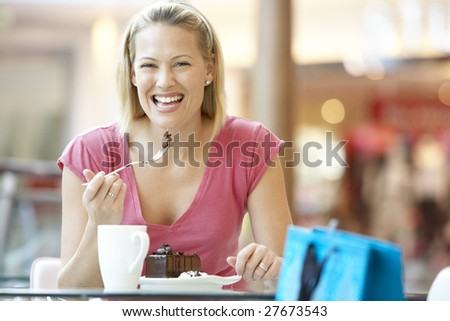 Woman Eating A Piece Of Cake At The Mall - stock photo