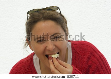 woman eating a strawberry with gluttony.