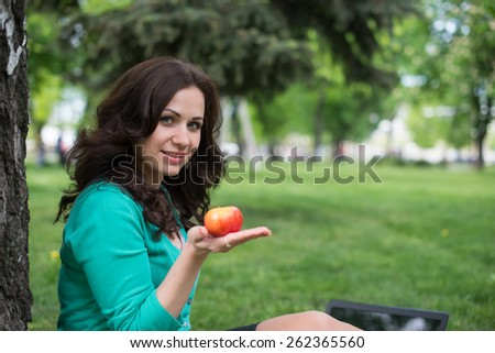 Woman eating an apple outdoors - stock photo