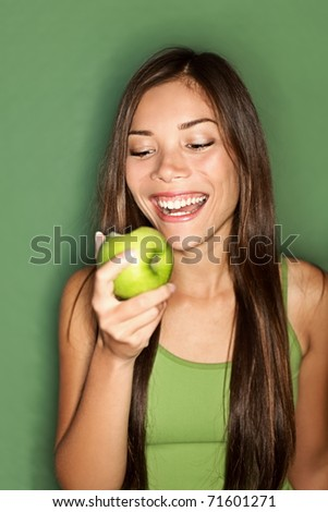 Woman eating apple smiling on green background. Healthy eating candid woman. - stock photo