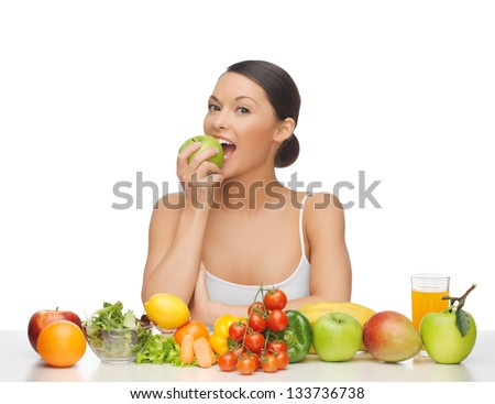 woman eating apple with lot of fruits and vegetables - stock photo