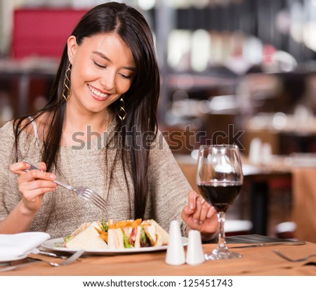 Woman eating at a restaurant looking very happy