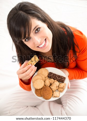Woman eating biscuits sitting on white bed indoor. Beautiful caucasian model. - stock photo