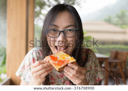 Woman eating bread with jam Breakfast at the hotel - stock photo