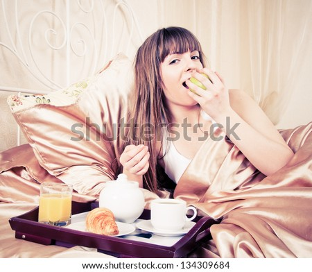 Woman eating breakfast and drinking coffee in bed. Young woman smiling looking at camera - stock photo