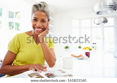 Woman Eating Breakfast And Reading Magazine - stock photo