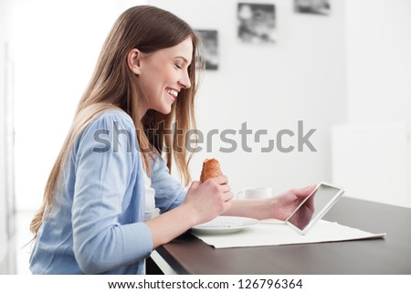 Woman eating breakfast and reading the news on digital tablet