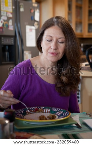 Woman eating breakfast at home in the morning - stock photo