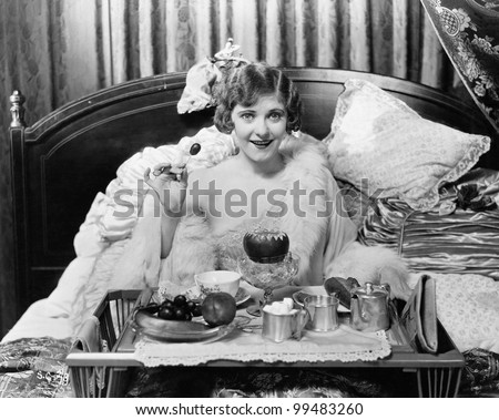 Woman eating breakfast in bed - stock photo