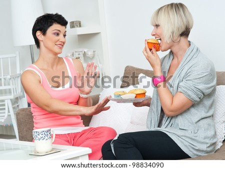 woman eating cakes and offering to her friend - stock photo