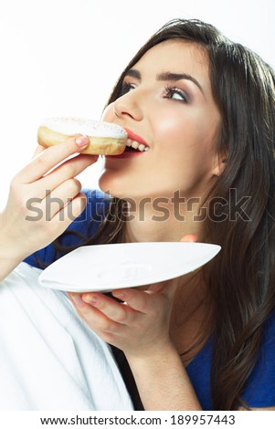 Woman eating donut in bed. Smiling girl.
