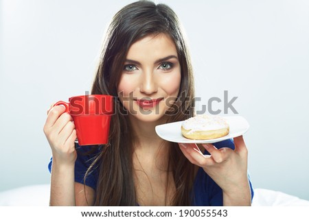 Woman eating donut in bed with coffee cup. Smiling girl.