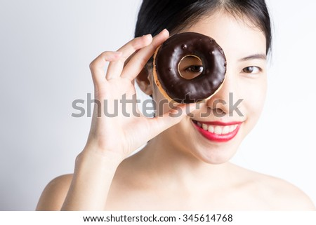 Woman eating donut on white background
