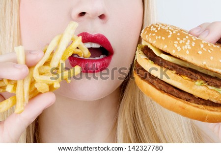 woman eating fast food - stock photo