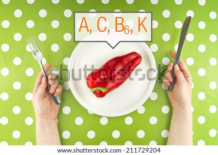 Woman eating fresh raw red pepper full of vitamins A, C, B and K, top view. - stock photo