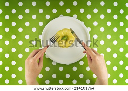 Woman eating fresh raw yellow pepper on a white plate, top view. - stock photo