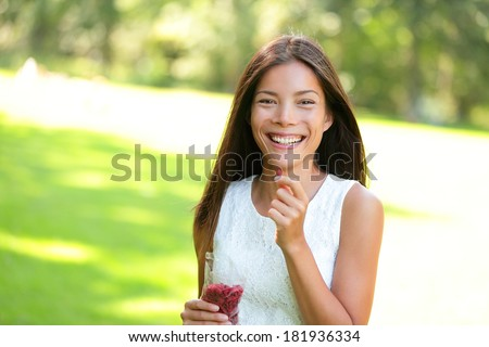 Woman eating goji berries healthy food snack outdoors in park. Healthy eating and lifestyle with beautiful mixed race Asian Caucasian female girl model. 20s - stock photo