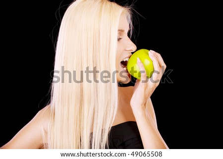 Woman eating green apple, isolated on black background.