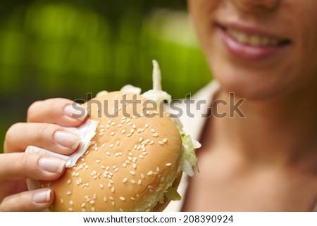 woman eating hamburger - stock photo
