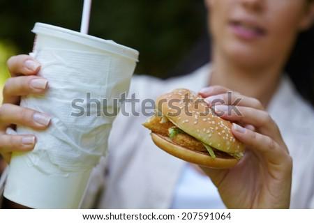 woman eating hamburger and cocktail - stock photo