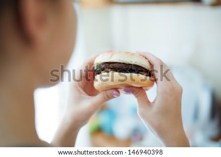 Woman eating hamburger. Rear view - stock photo