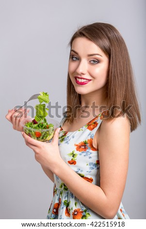 Woman eating healthy salad from plastic container. studio shot isolated on light  grey  background