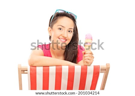 Woman eating ice cream seated on a sun longer isolated on white background - stock photo