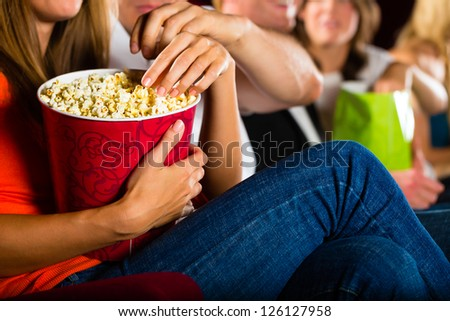 Woman eating large container of popcorn in cinema or movie theater - stock photo