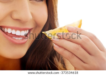 Woman eating lemon. - stock photo