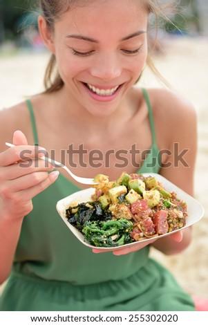 Woman eating local Hawaii food dish Poke bowl salad. Girl enjoying healthy lunch - a traditional local Hawaiian dish with raw marinated ahi yellowfin tuna fish. Healthy lifestyle concept. - stock photo