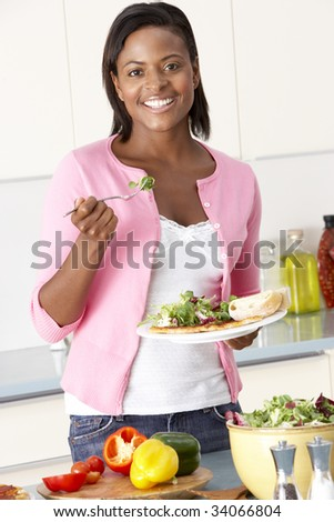 Woman Eating Meal In Kitchen