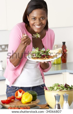 Woman Eating Meal In Kitchen - stock photo