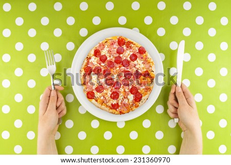 Woman eating pizza. Caucasian Female hands at dinner table holding fork and a knife above plate with served pepperoni pizza, top view - stock photo
