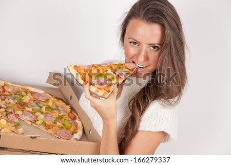 Woman eating pizza from pizza box, smiling looking at camera. Portrait of young woman model.