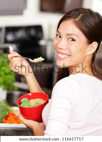 Woman eating quinoa / broccoli salad. Eat healthy food lifestyle concept with beautiful young multiracial woman in her kitchen.