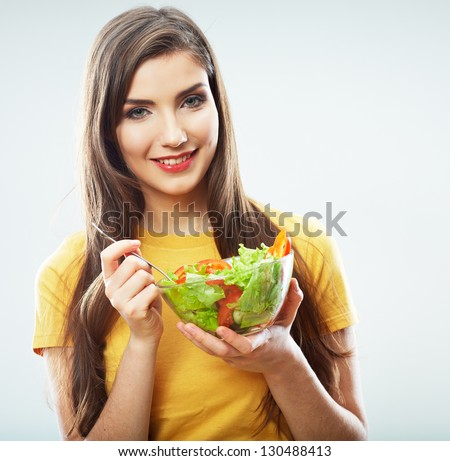 Woman eating salad . Female model studio isolated portrait .