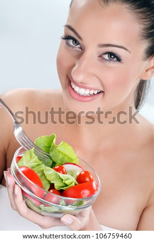 Woman eating salad,  portrait of beautiful smiling and happy woman enjoying a healthy salad - stock photo
