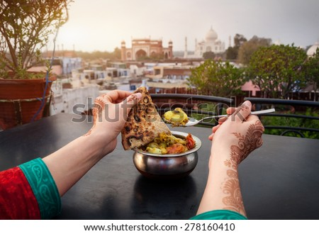 Woman eating traditional Indian food in rooftop restaurant with Taj Mahal view in Agra, Uttar Pradesh, India - stock photo