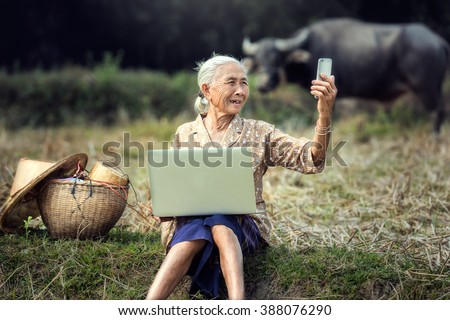 Woman elderly are using smartphone in selfie - stock photo