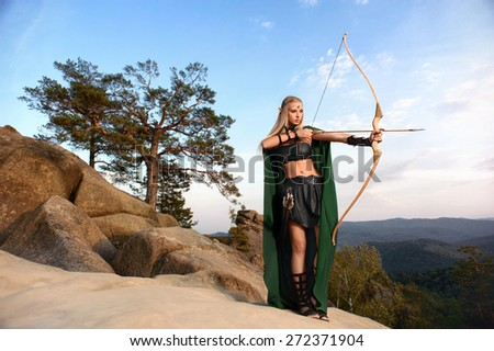 Woman elf warrior in the mountains against the sky the bow - stock photo