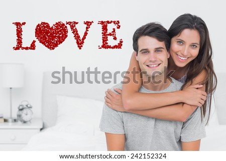 Woman embracing her partner against love spelled out in petals - stock photo
