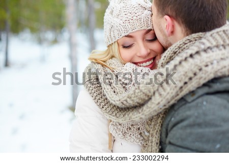 Woman embracing with her boyfriend in winter - stock photo