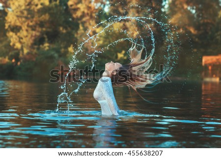 Woman emerged from the water, her hair spray droplets, she on a lake and forest.