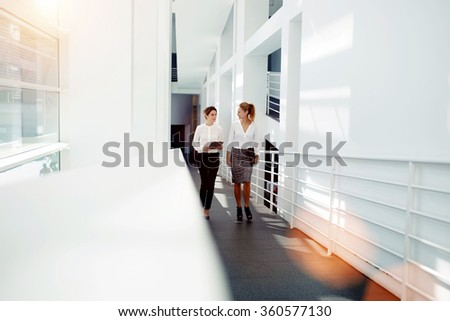 Woman employee holding touch pad and talk about ideas to the partner while walking in office hall interior, two female leaders exchanging information from digital tablet among themselves during break - stock photo