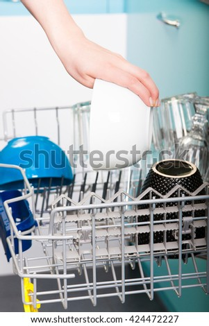 Woman empty out the dishwasher in kitchen