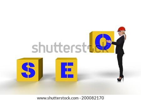 Woman engineer holding big yellow cube, seo concept - stock photo