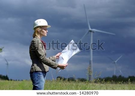 Woman engineer or architect with white safety hat and wind turbines on background