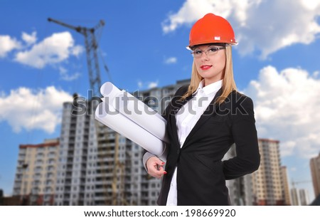Woman engineer with blueprint standing on buildings background
