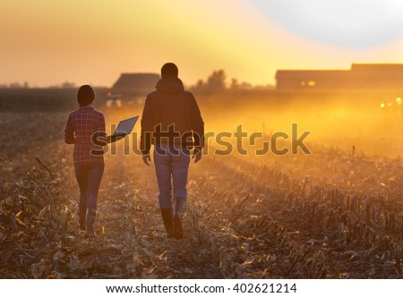 Woman engineer with laptop and landowner walking on harvested corn field during baling at sunset - stock photo